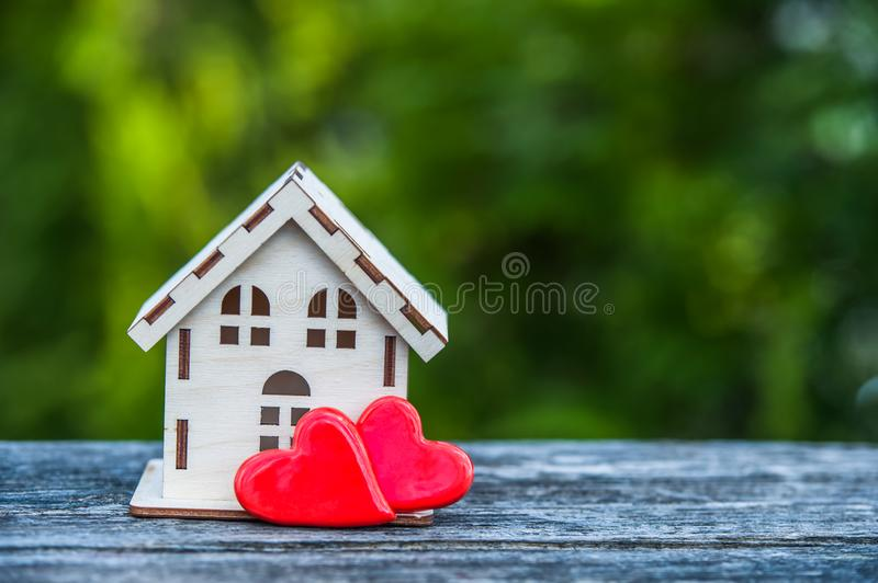 A toy house with a fence of hearts. A symbol of a house where love reigns. Theme of happiness, warmth, good luck, love, construction, travel, hotel business stock photography