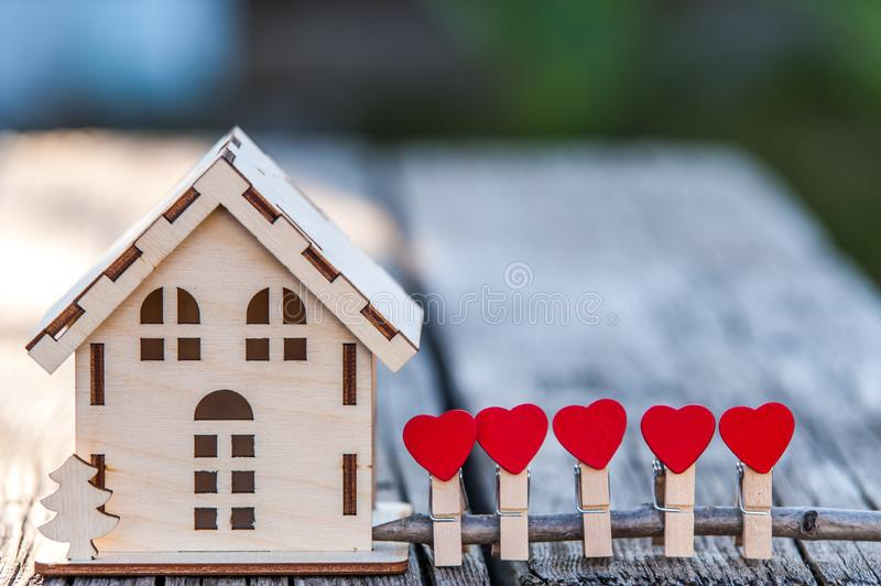 A toy house with a fence of hearts. A symbol of a house where love reigns. Theme of happiness, warmth, good luck, love, construction, travel, hotel business stock photos