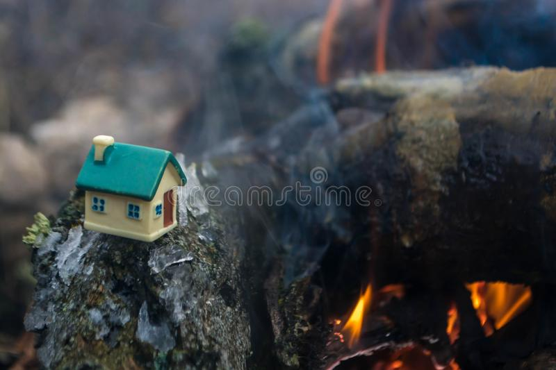 Toy house by the fire. In the open air, home, background, concept, white, christmas, dark, light, wooden, night, danger, heat, flame, burn, decoration, property stock images