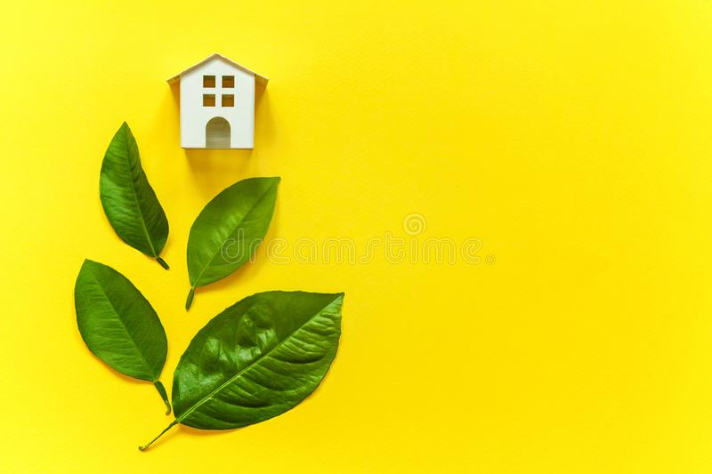 Toy House and green leaves. Miniature toy model house with green leaves on yellow colourful trendy backgdrop. Eco Village, abstract environmental background stock photos