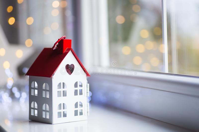 Toy house with hole in form of heart near window in daylight with garland lights on background. Romantic card. Valentine day banner royalty free stock image