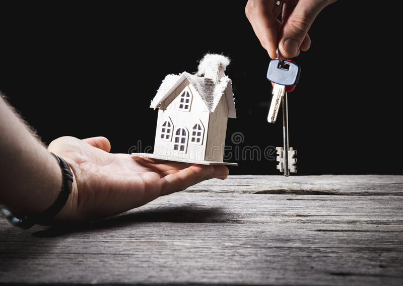Toy house with key on wooden background stock photos