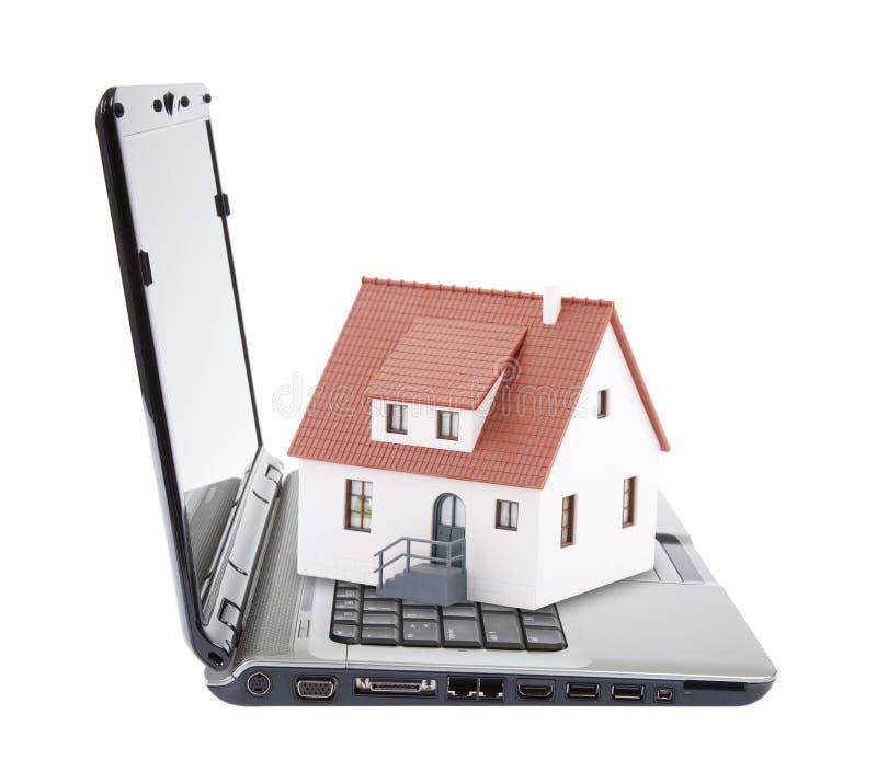 Toy house on laptop. Isolated on white stock photos
