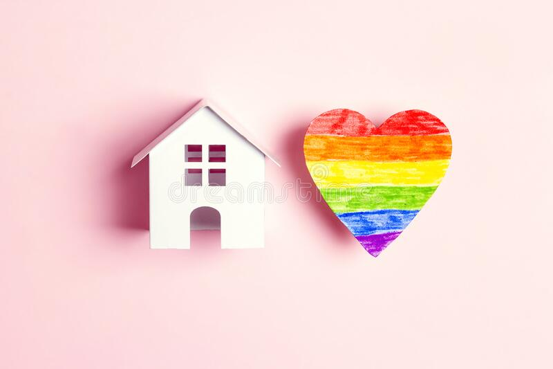 Toy house and lgbt rainbow heart on pink  background. Tolerance to homosexual and bisexual people community concept. Top view, flat lay stock photography