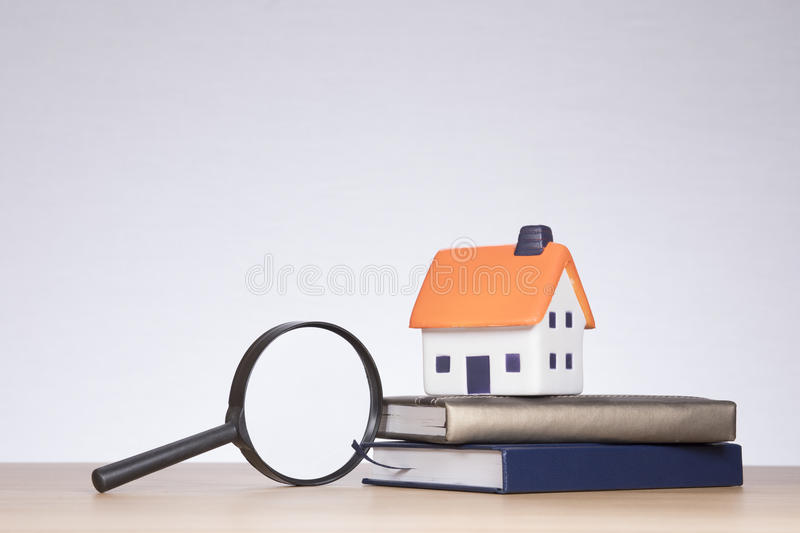 Toy house, magnifying glass and books royalty free stock photography