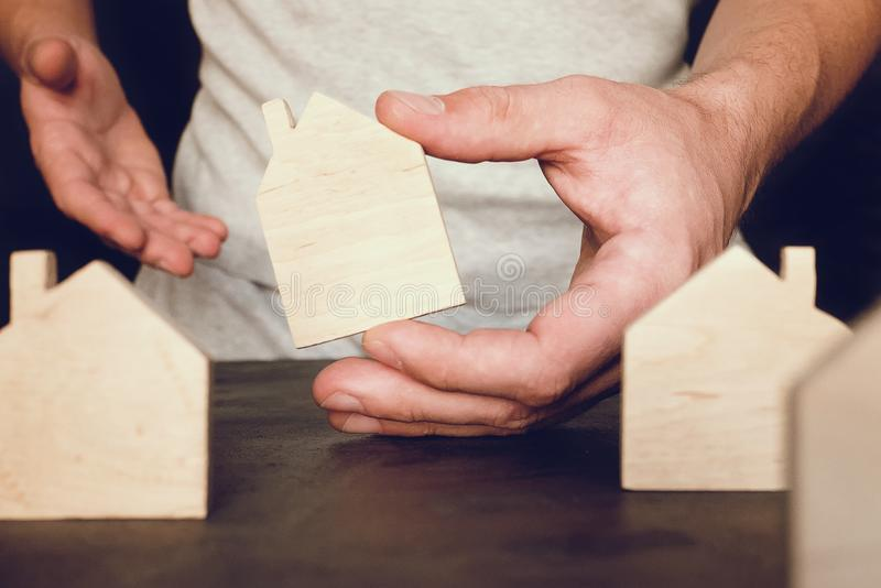 Real estate concept with wooden toy home in man hand. Toy house in man hand. Real estate concept with wooden toy home, block, build, hold, roof, sale stock photo