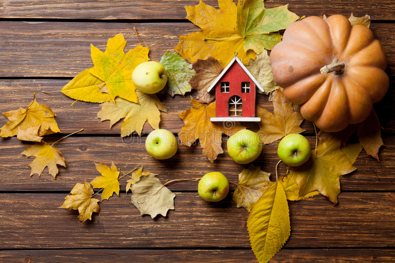 Toy house and pumpkin. With leafs on wooden background royalty free stock photography