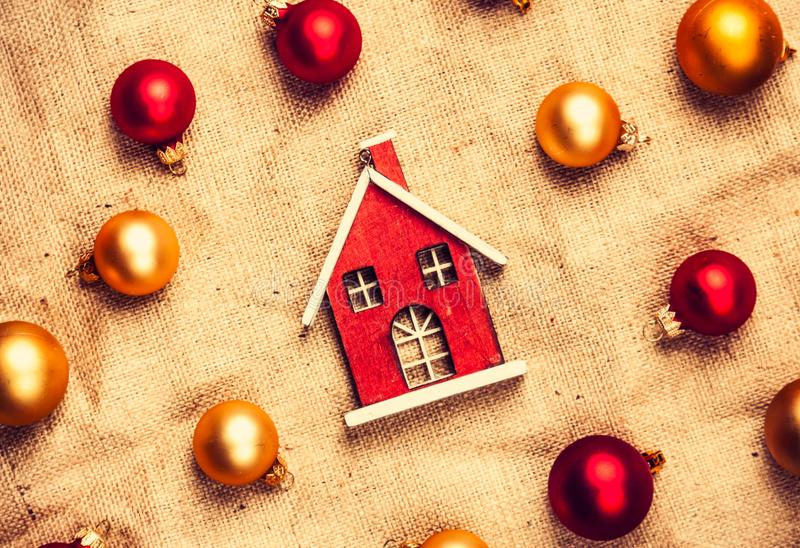 Toy house with red and gold baubles. On jute background stock photography