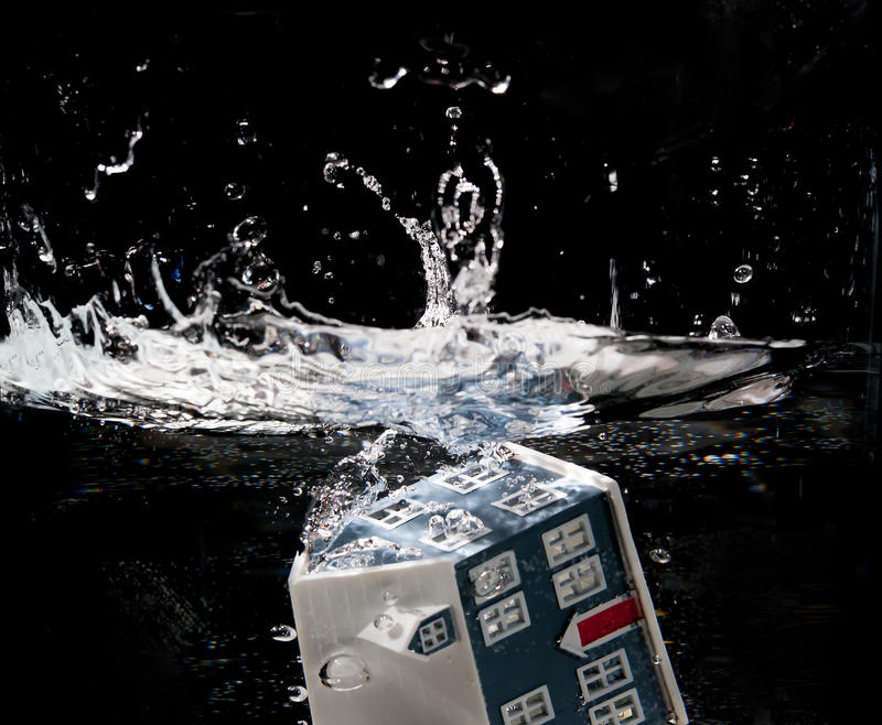 Toy house sinking. Underwater on a black background royalty free stock images