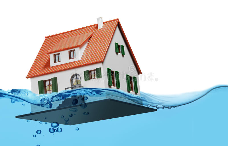 Toy house sinking underwater on a white background concept. Toy house sinking underwater on a white background showing flooding concept royalty free stock photo