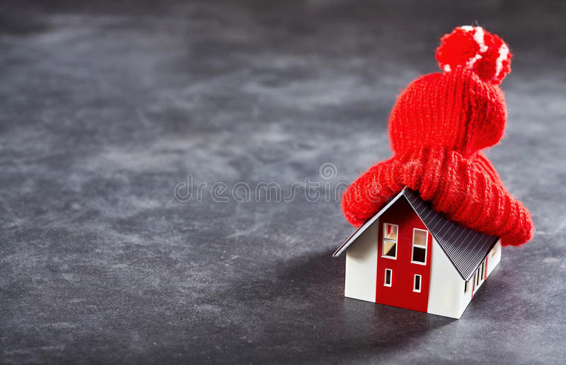 Toy house warming up with the hat. Small toy house with red knitted hat on its roof standing over dark surface royalty free stock photos