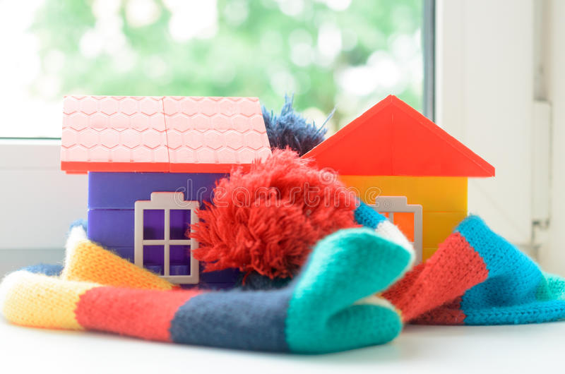 Toy house on the window sill wrapped in a scarf. Warming up the house. Toy house on the window sill wrapped in a scarf. Warming up the house royalty free stock images
