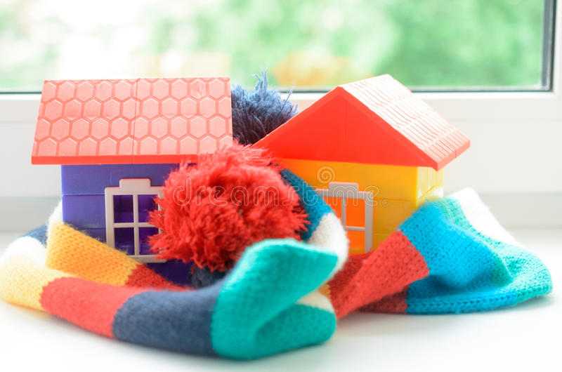 Toy house on the window sill wrapped in a scarf. Warming up the house. Toy house on the window sill wrapped in a scarf. Warming up the house royalty free stock photos