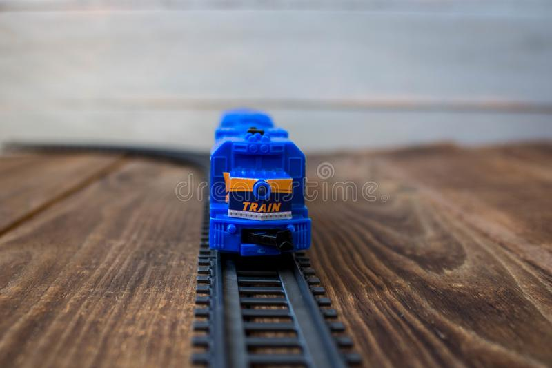 A toy locomotive on railway on wooden background stock images
