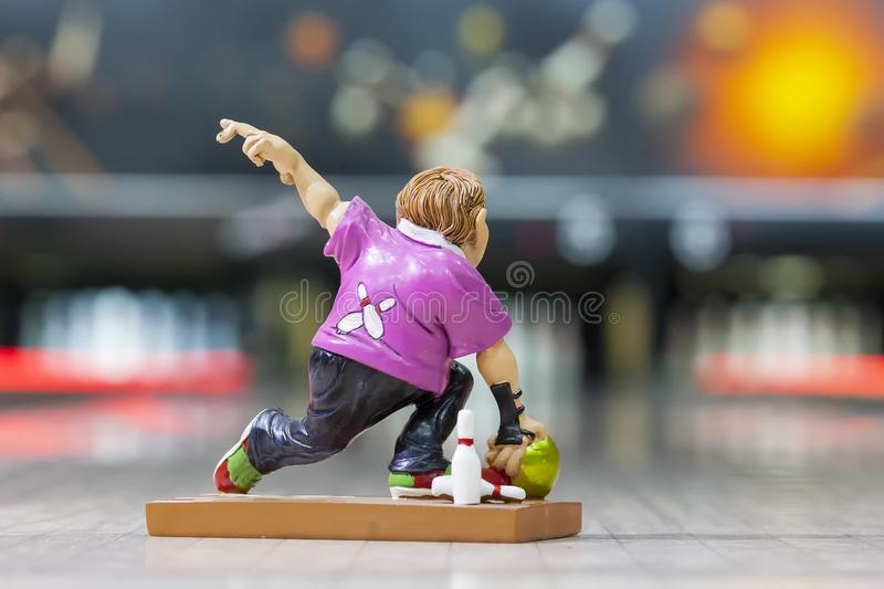 A toy man in a pink t-shirt throws a bowling ball against the background of a bowling playing field. Toy man in pink t-shirt throws a bowling ball on the royalty free stock photos