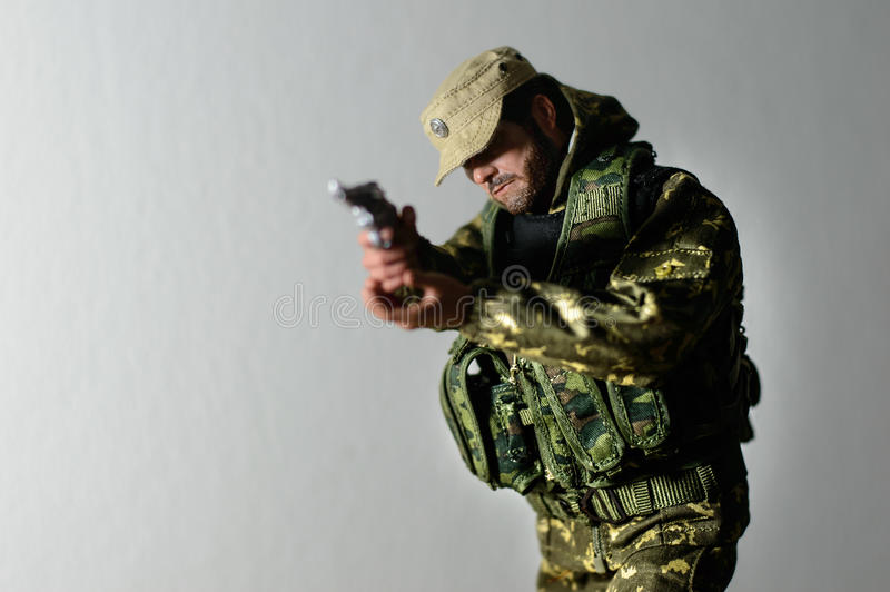 Toy man soldier action figure miniature realistic silk. Toy soldier shooting by hand gun miniature realistic authentic Military stock photo