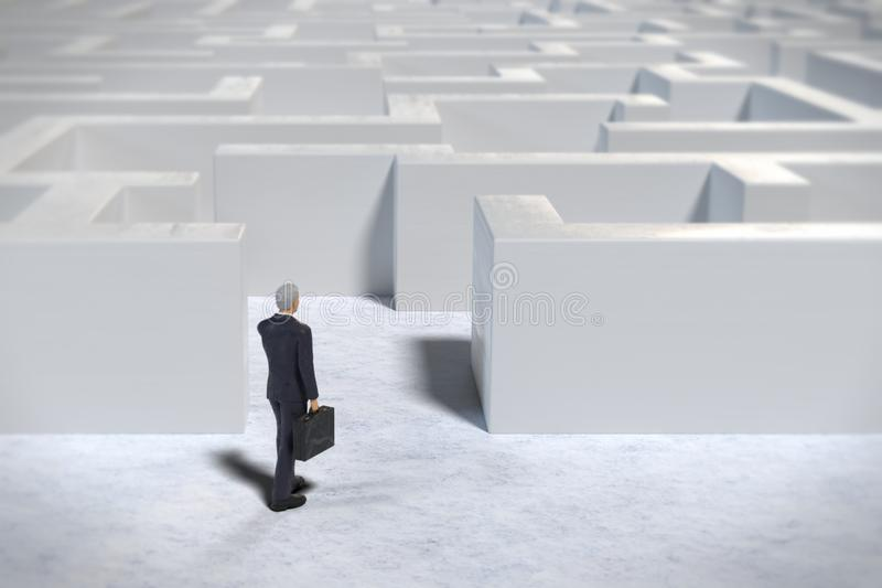 Toy miniature businessman figurine entering a white maze structure stock illustration
