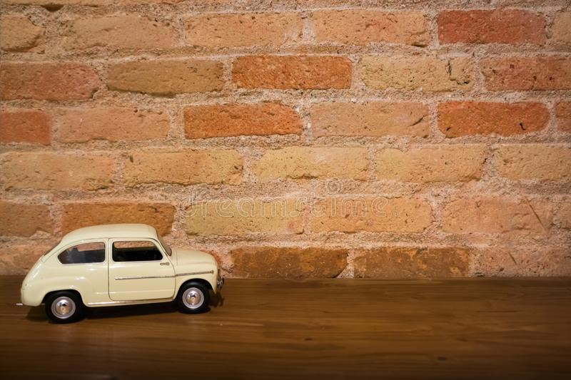 Toy model white retro car on a wooden surface against red brick background wall royalty free stock image