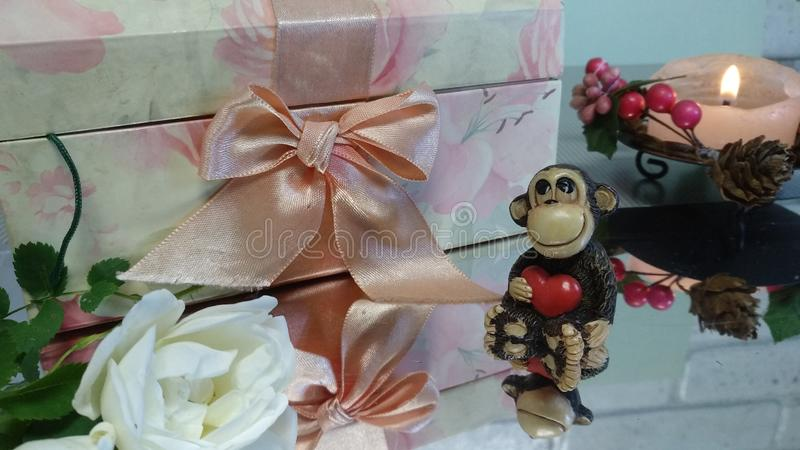 Toy monkey next to a white rose and a pink jewelry box stock photos