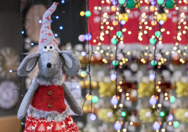 Toy mouse in knitted clothes on the background of festive garlands. Symbol of 2020 stock photography