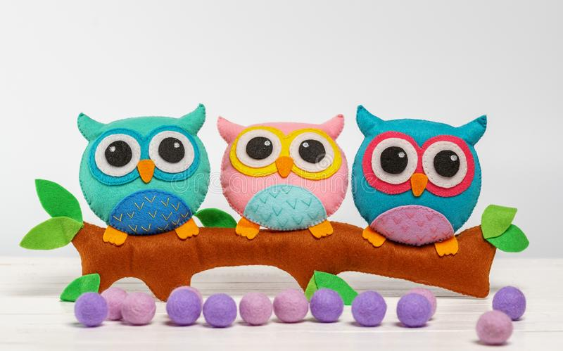 Toy owls handmade on a branch. light background. stock image