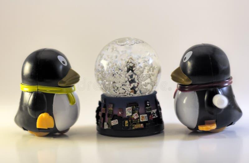 Toy Penguins Looking At Snow-Kugel lizenzfreie stockfotos