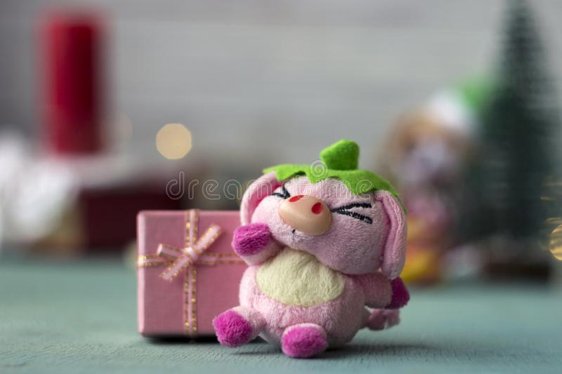 Toy pig and pink gift box on the background of Christmas accessories, background royalty free stock image