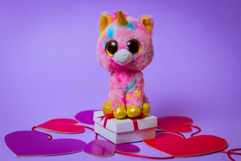 Toy Pink Unicorn sitter på en vit gåvaask med ett rött band på pappers- hjärtor på en purpurfärgad bakgrund arkivbild