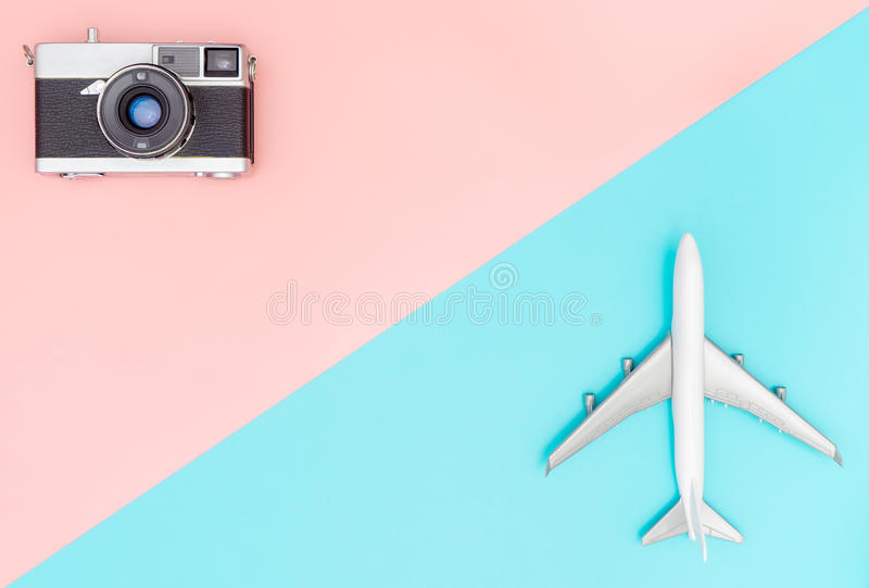 Toy plane and camera on pink and blue background royalty free stock images