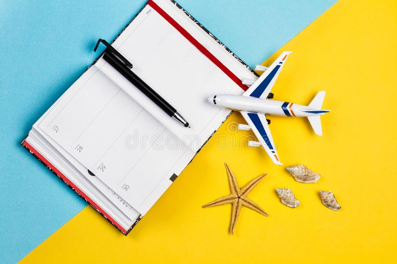 A toy plane and a diary with a pen. On a yellow and light blue background stock photography
