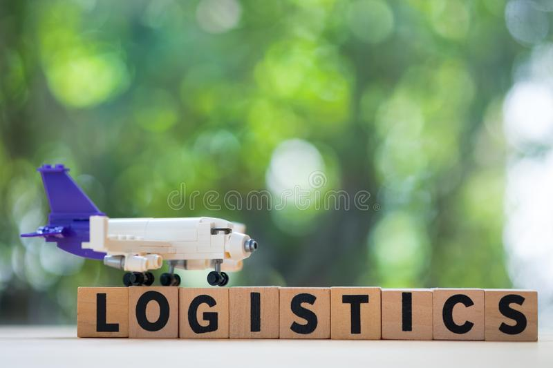 Toy plane model put on wooden blocks word of logistics with natural background. Logistics and transportation management ideas and Industry business commercial stock image