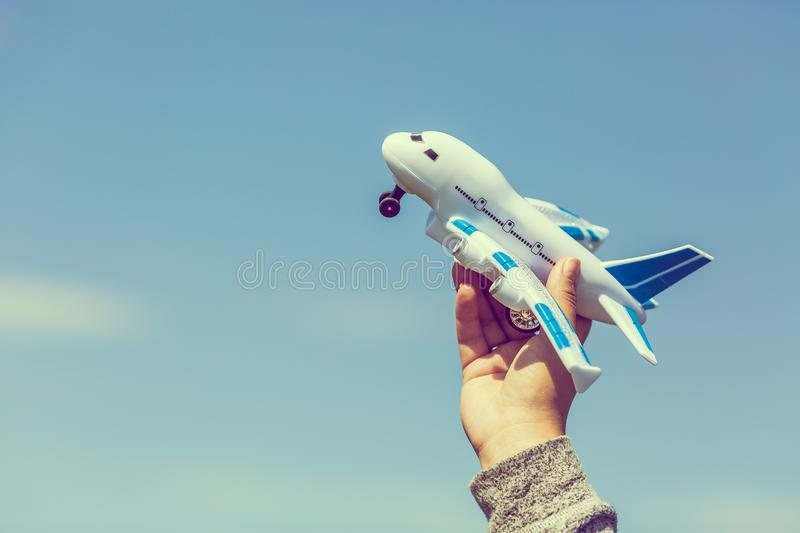 Toy plastic airplane in hand against blue sky. Dreams, vacation or travel concept. Vintage toned effect. stock image
