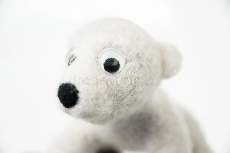 Toy polar bear made of felted wool looking at you from the white background. A toy polar bear made of felted wool looking at you from the white background stock image