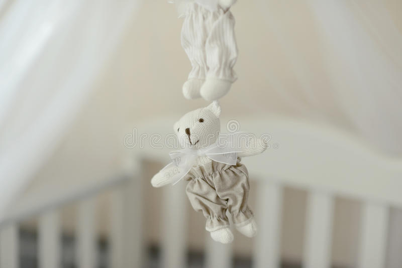 Toy polar bear. Near the crib hanging white teddy bear toy handmade stock image