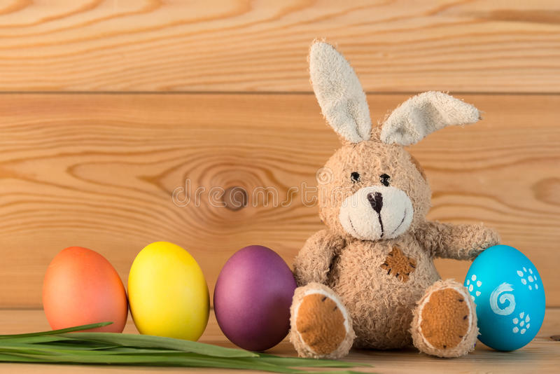 Toy rabbit with Easter eggs on wooden background stock images