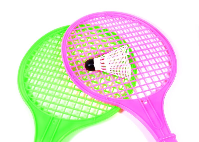 Toy racket with shuttlecock ball. Two plastic toy rackets and shuttlecock ball with isolated white background royalty free stock photography
