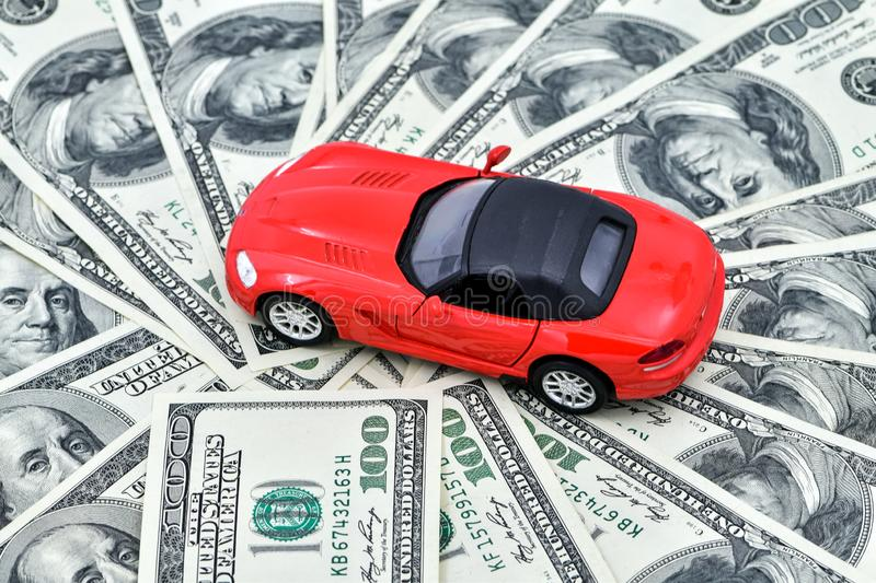 Toy red car and a pot of money dollar bills. Good time to buy a car on credit, save up for a vehicle. stock photography