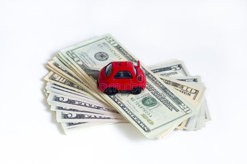Toy red car and a stack of money dollar bills American dollars on a white isolated background. buy a car on credit. royalty free stock photos
