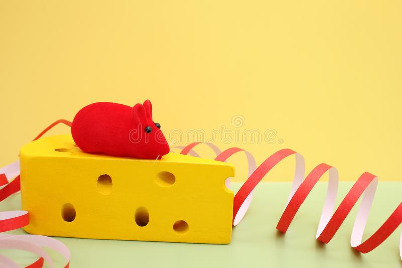 Toy red mouse on toy yellow cheese. Mouse-symbol of New year 2020 stock images
