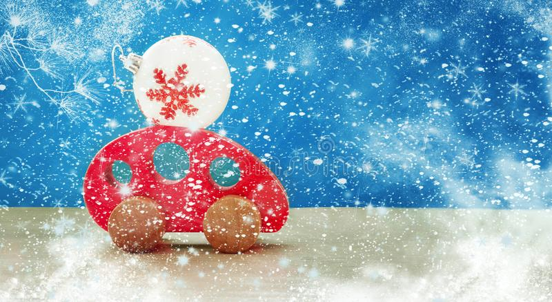 Toy red wooden car carries a Christmas ball. Merry Christmas and New Year holiday background stock image