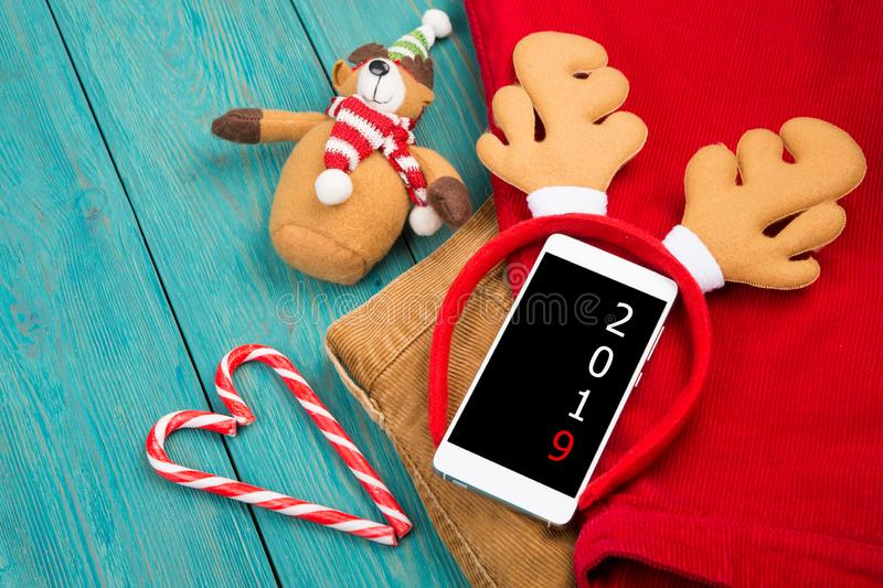 Toy reindeer antlers, smartphone with text `2019`, teddy bear, candy and clothes stock photo