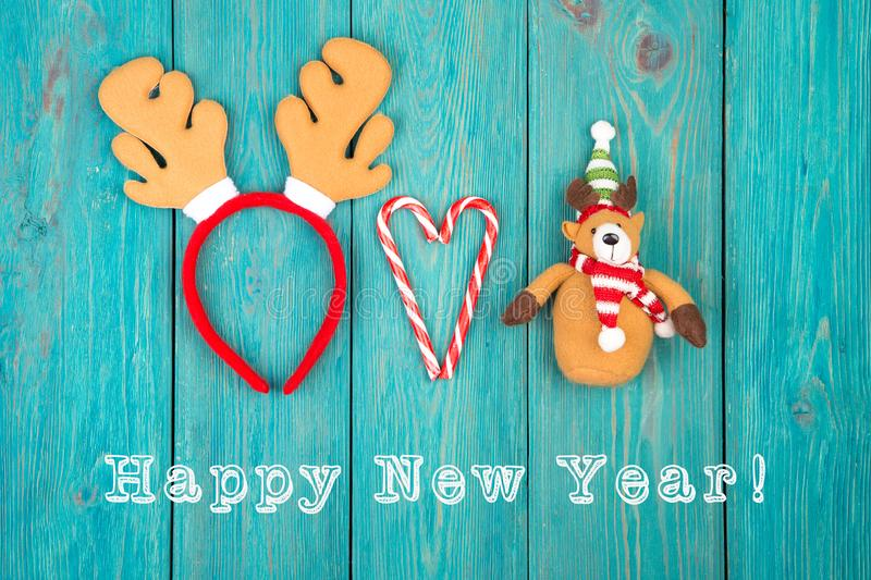 "Toy reindeer antlers and teddy bear, candy and text ""Happy new year. "" on blue wooden desk royalty free stock images"