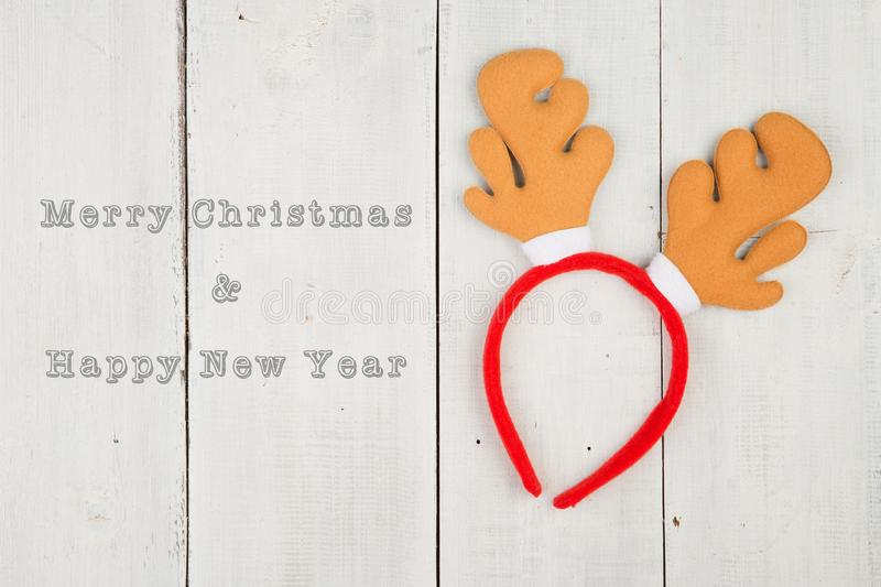 Toy reindeer antlers on a white wooden desk and text. `Merry Christmas & Happy New Year royalty free stock photography