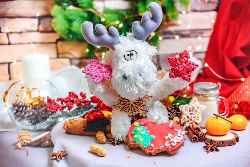 Toy reindeer with stars in hands, tangerins, cookies and bright star shape bokeh royalty free stock photos