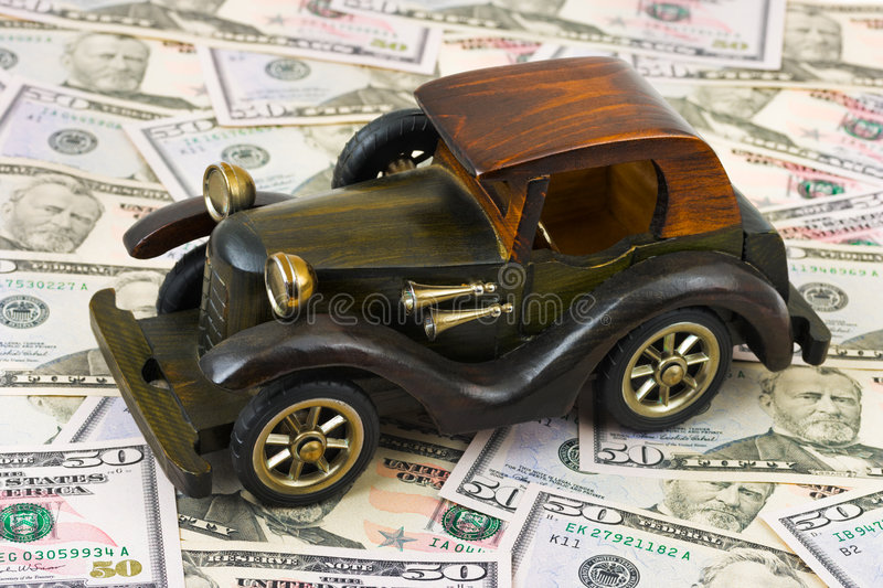 Toy retro car on money background. Business concept stock photo