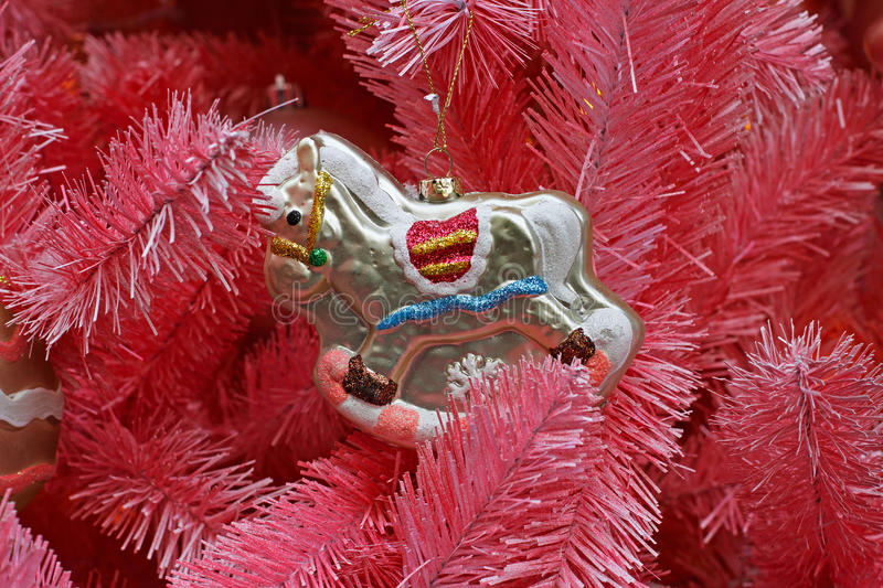 Toy rocking horse hanging on the branch of pink Christmas tree royalty free stock image