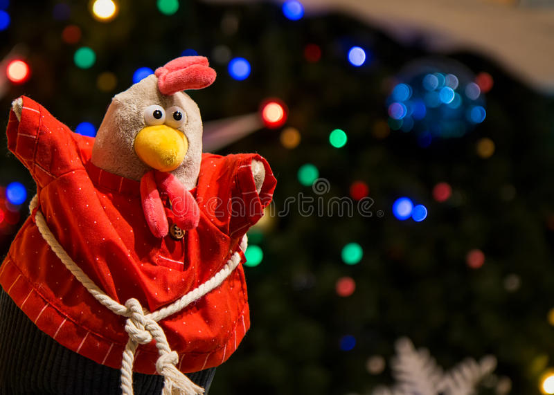 Toy rooster under the Christmas tree. The symbol of the new year 2017. Christmas decorations. New Year decoration Christmas tree stock image