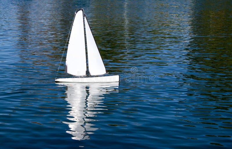 Toy Sailboat blanco en una charca azul fotos de archivo libres de regalías