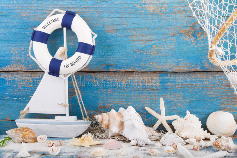 Toy sailboat and life buoy with seashells and starfish an a wood stock photography