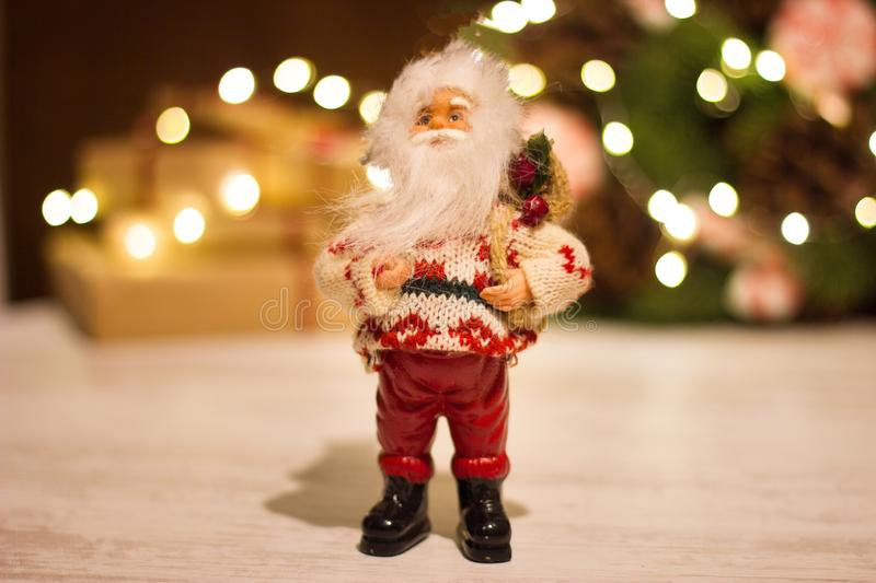 Toy Santa Claus on the background of gift boxes and a Christmas wreath with a luminous garland stock photography